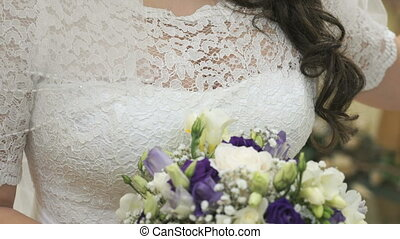 Bride dressed white dress holding a bridal bouquet at...