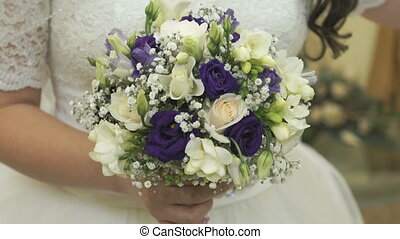 Bride clothed white dress holding a bridal bouquet at...