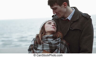 Young couple looking at the sea, hug at the beach, coat and...