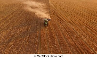 Tractor with plow in motion. Process of plowing field.