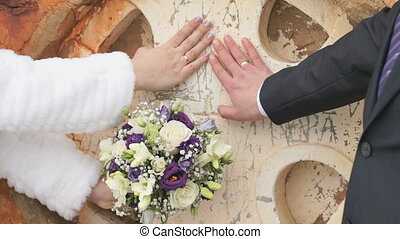 Newlyweds put hands with rings to wall of church in the form...