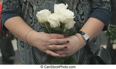 Woman stands and holds bouquet of five white roses during...