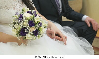 Bride and groom sitting on couch hold hands at room of...