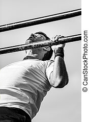 Male doing pull ups on competition