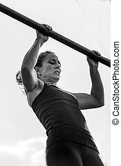 Female doing pull ups on competition