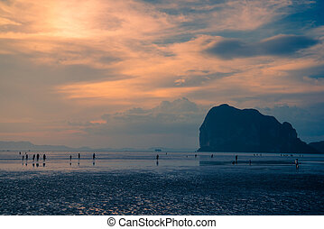 Many travelers on beautiful beach in sunset at...