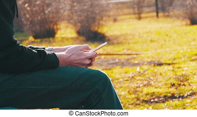 Woman using a Mobile Phone on a Bench in the Park - Girl...