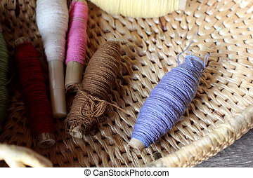 colorful bobbins of thread in basket