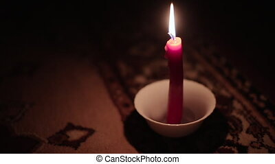 One candle burning in a saucer. Video full hd.