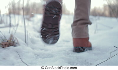 Camera pursues human legs that walks through the snow in the...