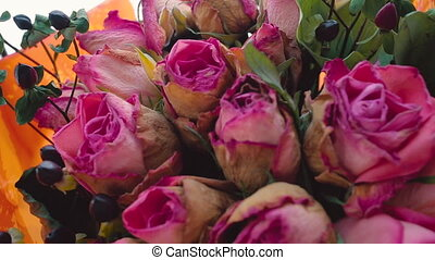 Faded bouquet of pink roses is spinning around its axis....