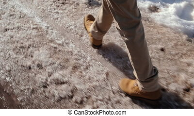Camera pursues human foot that is on the dirty snow in the...
