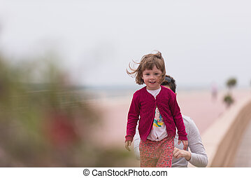 mother and cute little girl on the promenade by the sea -...
