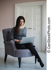 Young woman with laptop sitting on armchair at home.