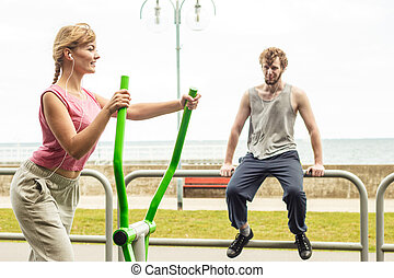 Man and woman exercising on elliptical trainer. - Active...