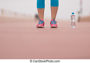 close up on running shoes and bottle of water - Fitness...