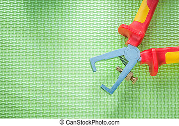 Insulated wire strippers on green background electricity...