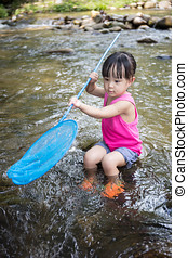 Asian Chinese little girl catching fish with fishing net