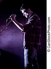 man with microphone on a black background, the music...