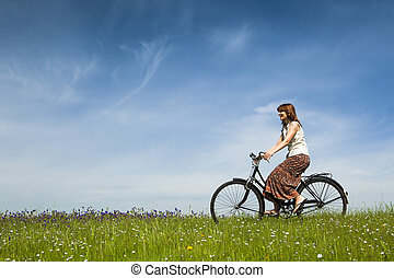 Riding a bicycle - Happy young woman on a green meadow...