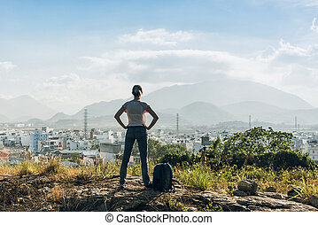 Woman on a top of a hill - Fashionable girl in dark blue...
