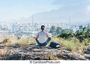 woman on top of the hill meditating - Fashionable girl in...