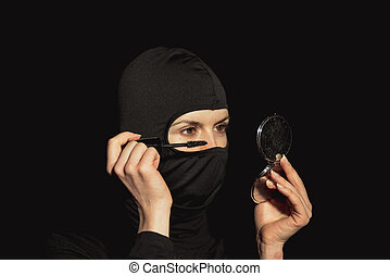 Girl offender. The girl in a black mask paint eyelashes.