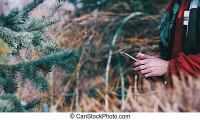 Young Man using a Mobile Phone in the City Park