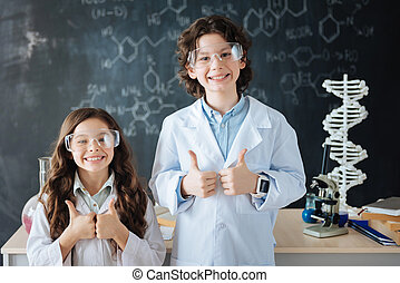 Cheerful little researchers enjoying science class at school...