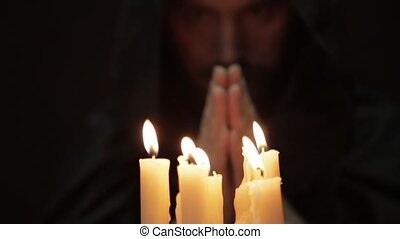 man doing the magic ritual. close-up several candle and old...
