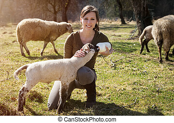 Woman is feeding a lamb with bottle of milk, animal welfare and rearing