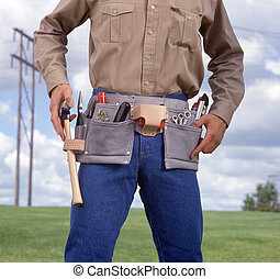 Man with tool belt blue sky and electrical pole in the...
