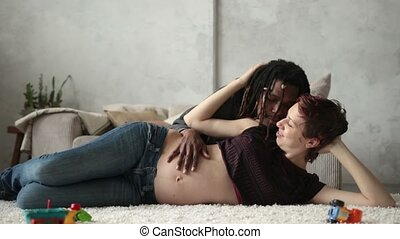 Pregnant woman with husband lying on the floor