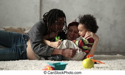 Interracial family with child playing on the floor -...