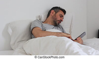Man use tablet in bed - Shot of Man use tablet in bed