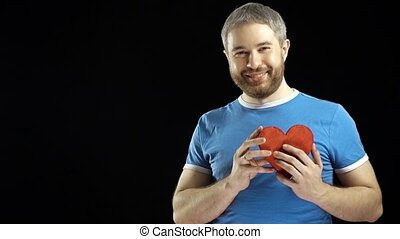 Smiling bearded man in blue tshirt giving red heart shape. Love, romance, dating, proposal concepts. Black background. 4K video