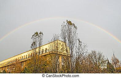 Vibrant colored rainbow over blue cloudy sky, european city, autumn vegetation