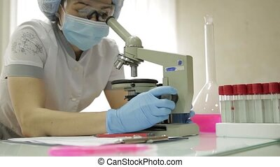 female medical researchers working with microscopes and test tubes in laboratory conditions, investigates and takes notes