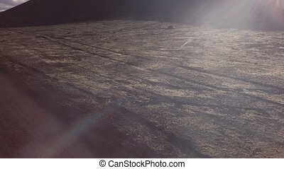 Rays of sun shine in camera along road at old lava fields on...