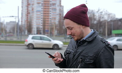 Attractive man looking at mobile phone while waiting in city bus stop
