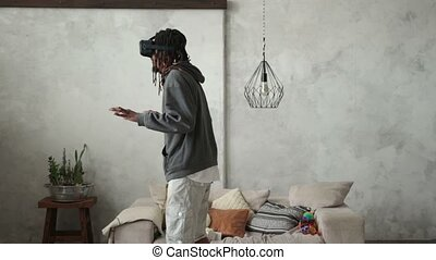 Playful hipster man wearing virtual reality device - The...