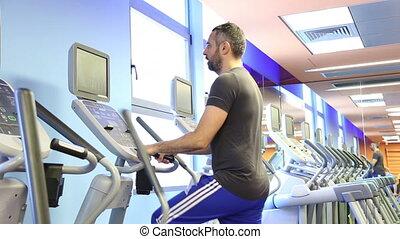 Man on elliptical fitness equipment - Shot of Man on...