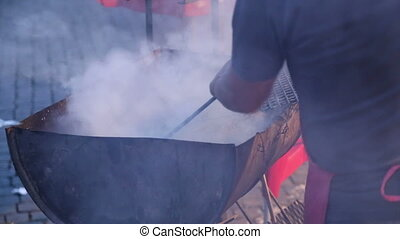 Man mixing charcoal in a smoky grill - Shot of Man mixing...