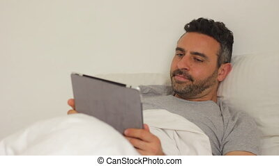 man in bed with tablet - Shot of man in bed with tablet