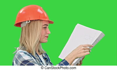 Female construction engineer reading plans and talk to workers on a Green Screen, Chroma Key.