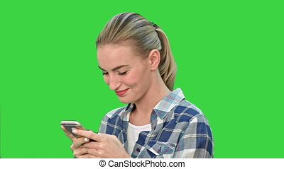 Young woman smiling while texting a message via cell phone on a Green Screen, Chroma Key.