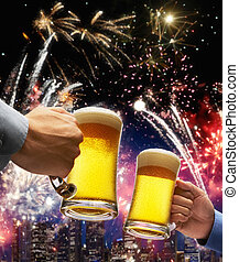 celebration - beer toasting with firework and skyline as...