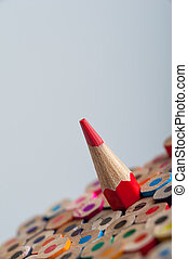 Red sharpened pencil among colorful crayons. Pencils...