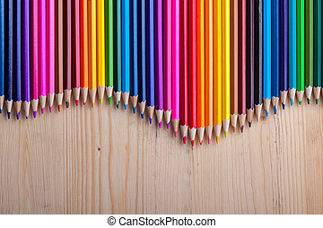 Multicolored pencils on wooden table, top view. Wooden...