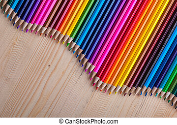 Multicolored pencils in wave form on wooden table. Bright...